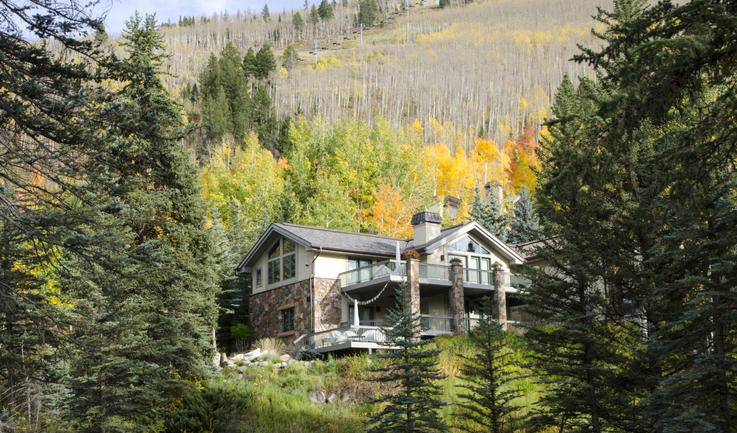 Vail, Colorado, USA - October 1, 2015: A Multi-million dollar home has been built along the Gore River in Vail, Colorado. The village was established and built as the base village to Vail Ski Resort, with which it was originally conceived and is the third largest ski mountain in North America. Vail attracts wealthy visitors, many of whom, who build and purchase vacation homes and condominiums near the ski slopes. Each Autumn, the Colorado Rocky Mountains create a dazzling and colorful display as the Aspens turn a brilliant yellow and glow against the mountains. In addition, their tall, vertical, trunks with white bark create a repetitive pattern under the foliage.