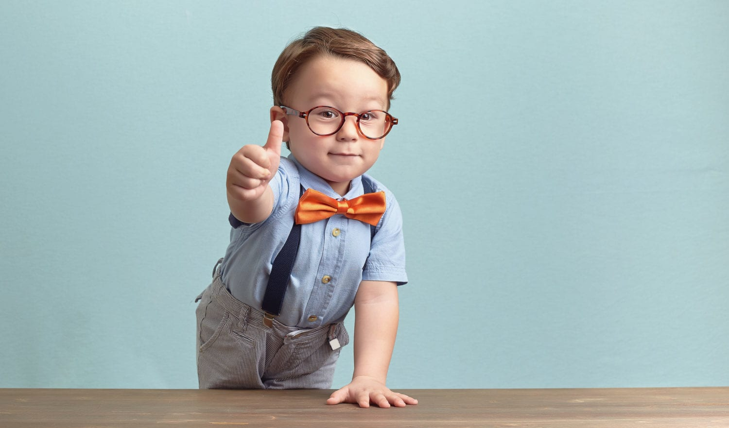 Around three years old boy in an orange bow tie and glasses, wearing blue shirt. He is smiling while giving you thumbs up over baby-blue backgorund, behind the brown table, left hand up on the table. Photo was taken by Canon DSLR.