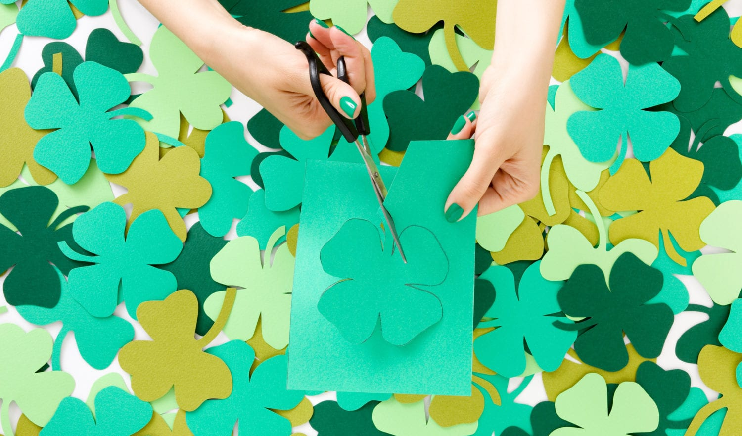Young woman cutting green paper clovers