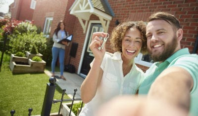 a young couple celebrate getting the keys to their new home by taking a selfie in the garden . IN the background the letting agent completes the paperwork.
