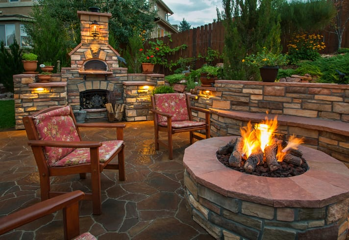 Beautiful backyard at twilight that includes a pizza oven and fire pit.