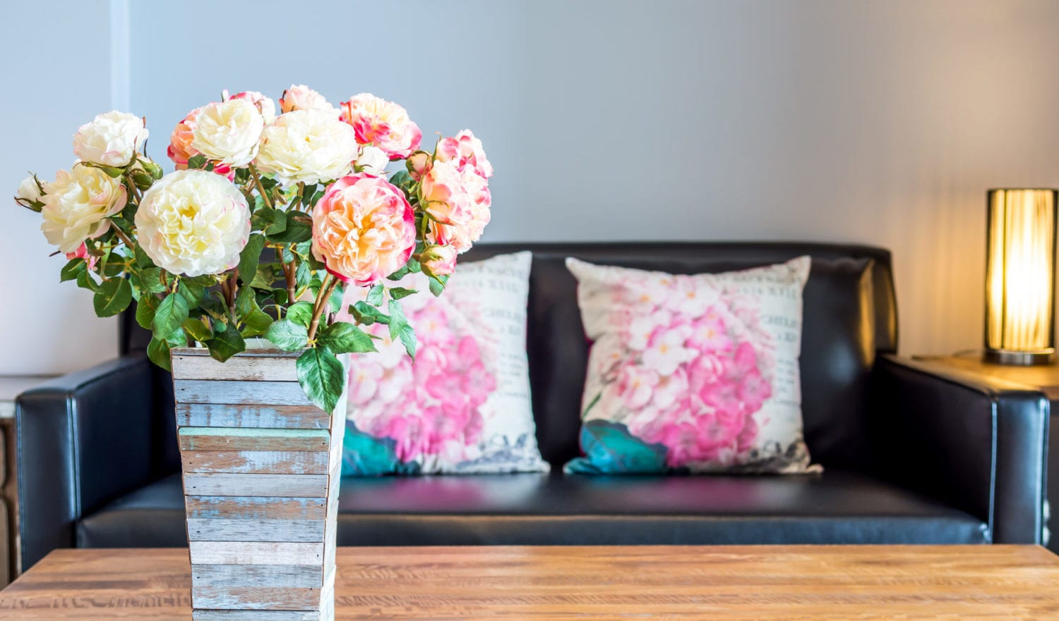 Modern interior room decorated with artificial flowers in rustic wooden vase