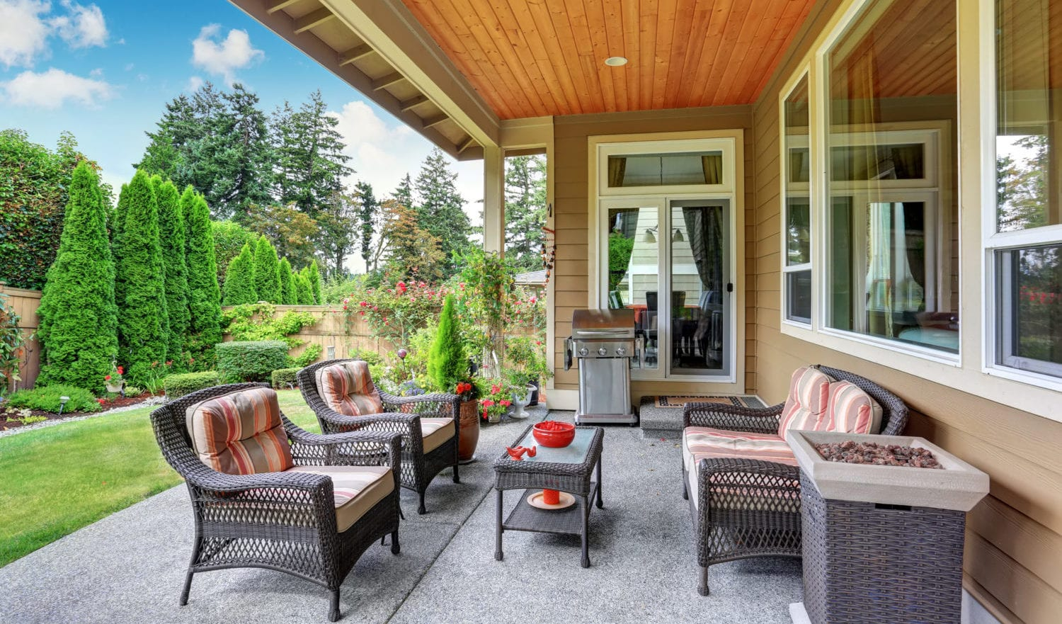 Cozy covered sitting area with wicker chairs and barbecue. Northwest, USA