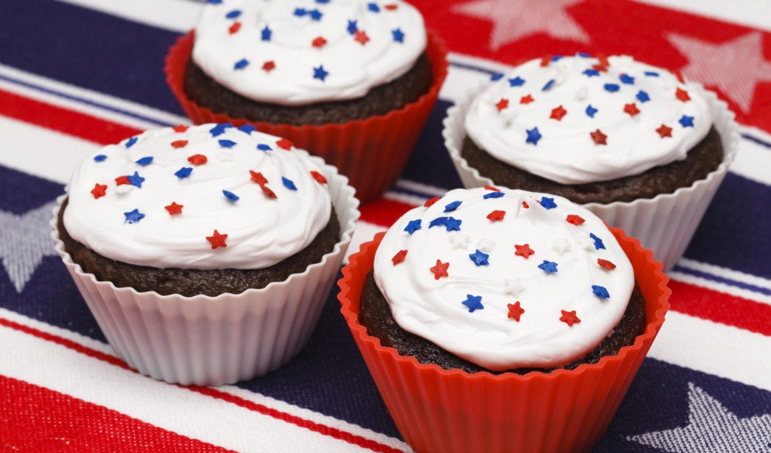 """Red, white and blue cupcakes with stars on a patriotic table cloth"""