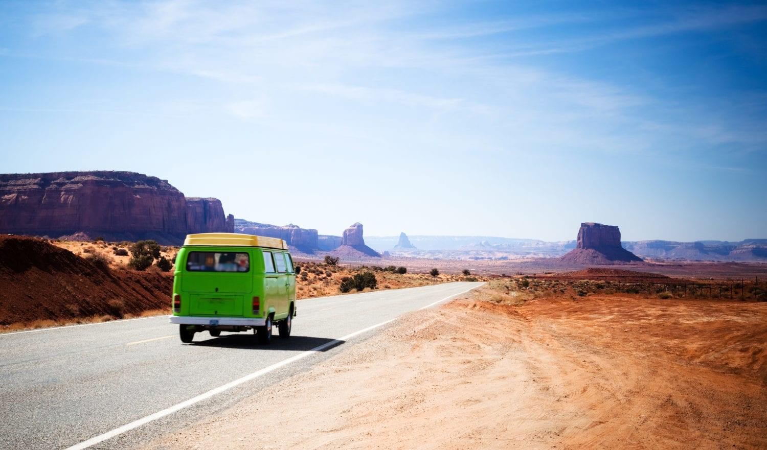 Green van driving on the Highway 163 in the Monument Valley between Utah and Arizona during a bright blue day. Car in motion.