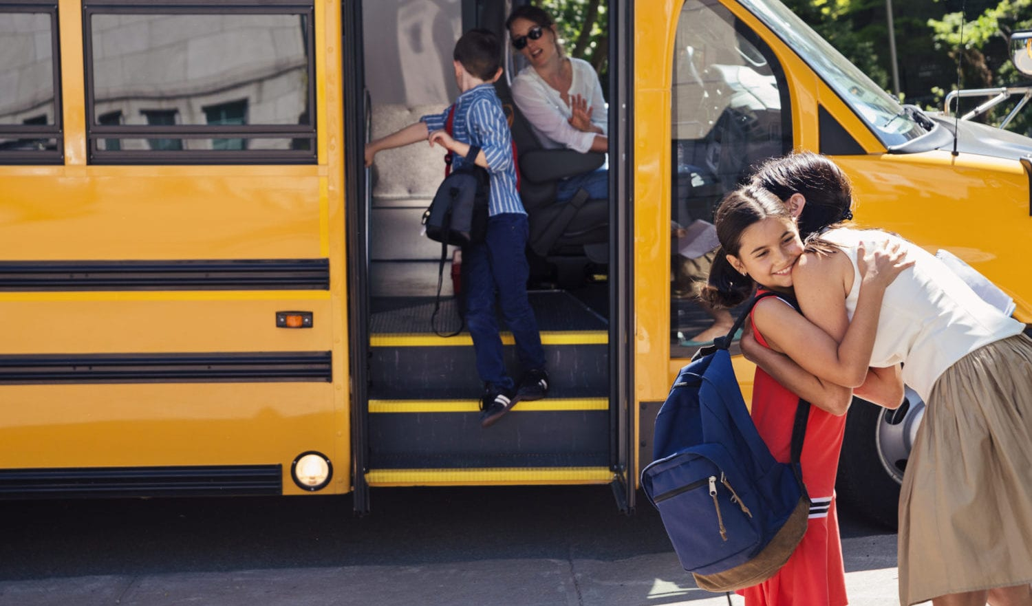 Mother greeting elementary age girl getting off yellow school bus. Little boy saying goodbye to the driver in the background. Woman is driving the bus. Horizontal outdoors shot with copy space. This was taken in Quebec, Canada.
