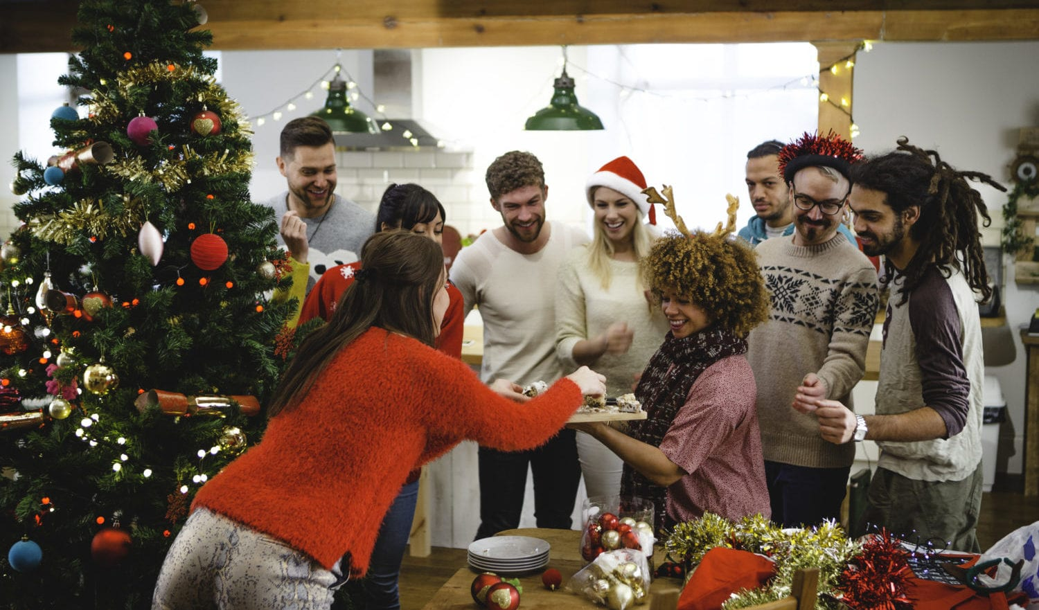 A group of friends are decorating the Christmas tree together. A woman is holding some cake and all the friends are digging in and enjoying themselves.