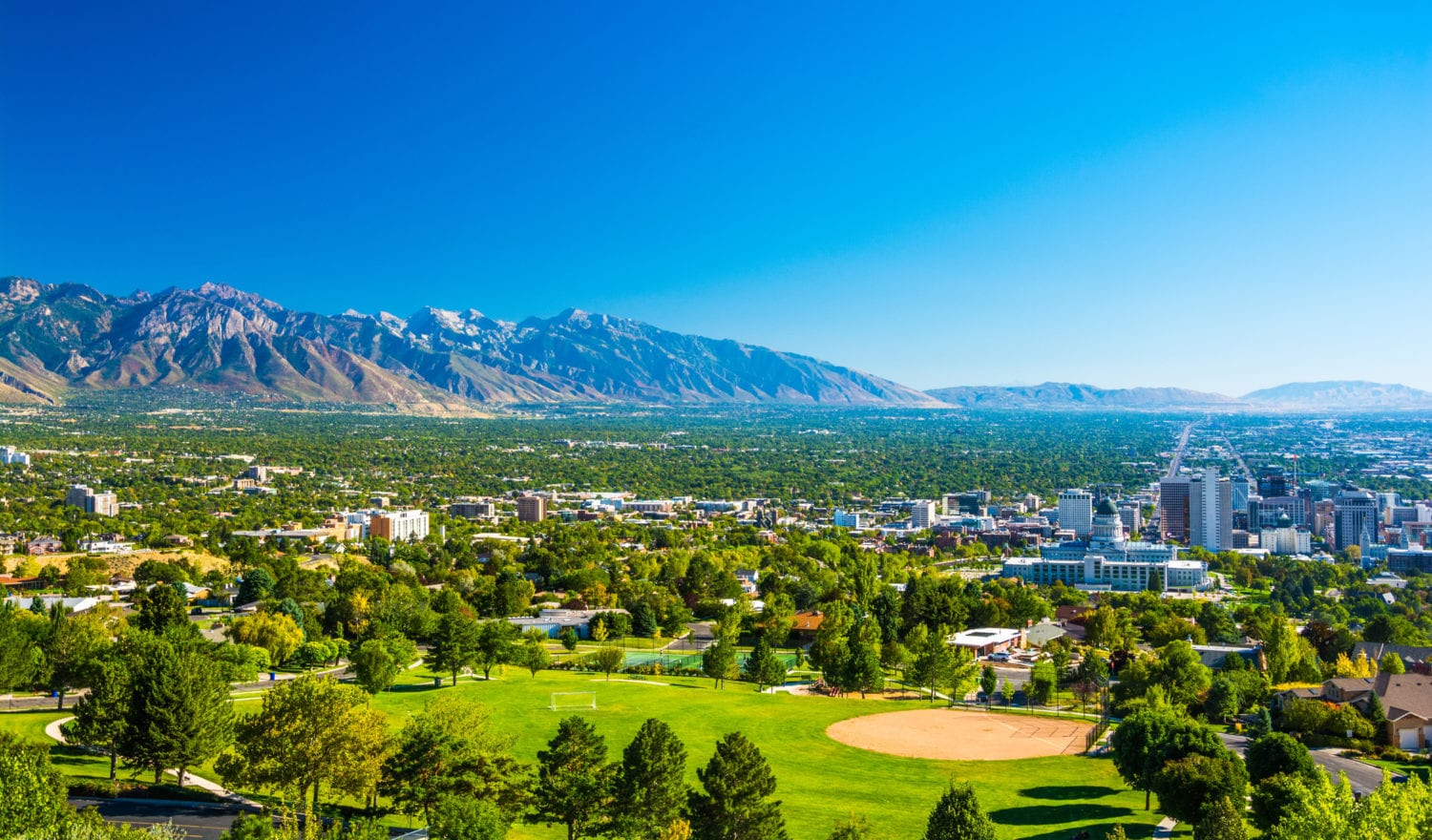 Salt Lake City aerial skyline view with a park in the foreground, downtown to the right, and the Wasatch Range mountain range far in the distance.
