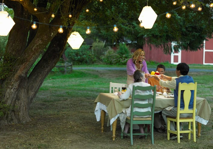 Four people dining in yard at dusk